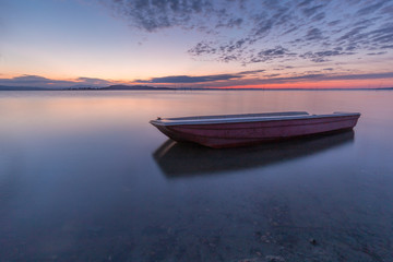 A little fishing boat in the middle of perfectly still water at dusk