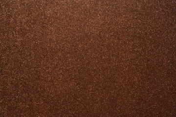 Brown glitter abstract shiny background. Design paper texture for decoration and design of Christmas, New Year or other holiday pictures. Beautiful packaging material.