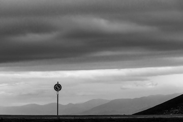 Road sign against a moody sky background with big clouds