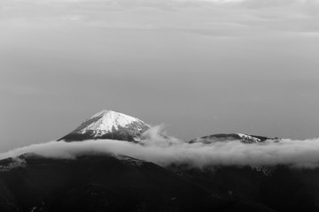 Mountain top covered by snow in the middle of clouds