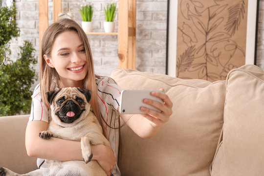 Beautiful young woman with cute pug dog taking selfie at home