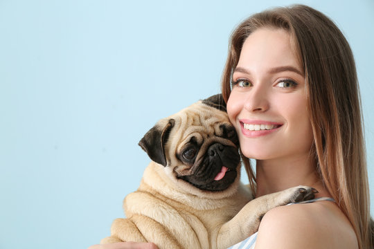 Beautiful young woman with cute pug dog on color background