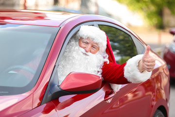 Santa Claus showing thumb-up gesture while driving car