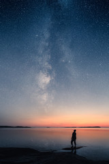 Fototapeta A man standing by a calm sea and looking up on the stars of the milky way obraz