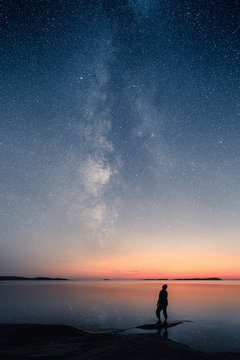 A man standing by a calm sea and looking up on the stars of the milky way