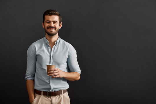 Drinking cappuccino. Cheerful young bearded man holding a cup of hot coffee and looking at camera with smile while standing against dark background