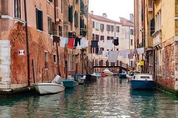 Venice, Veneto, Italy - A narrow canal in Venice is traditionally used to dry clothes by tying a line to the house and boats can ride underneath.