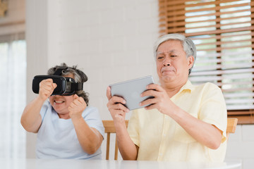 Asian elderly couple using tablet and virtual reality simulator playing games in living room,...