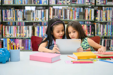 Two little happy cute girls playing on a tablet PC computing device in library at school. Education and self learning wireless technology concept. People lifestyles and friendship. Preschool children Fototapete