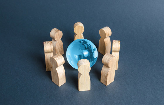 People surrounded a blue glass globe. Concept of cooperation and collaboration of people and countries around the world. The Big Eight. Outsourcing and joint work on projects. Diplomacy. crowdfunding