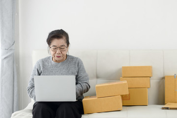 Asian senior woman using laptop while selling online with packaging, work at home concept. Fototapete