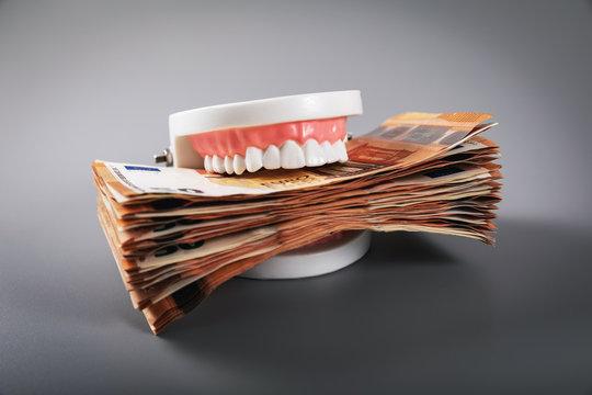 greediness concept - teeth model eating euro money bills