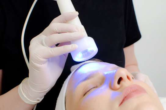 beautician applying blue led light therapy to female customer in beauty salon, facial photo therapy for skin pore cleansing. Anti-aging treatments and photo rejuvenation procedure extreme close up