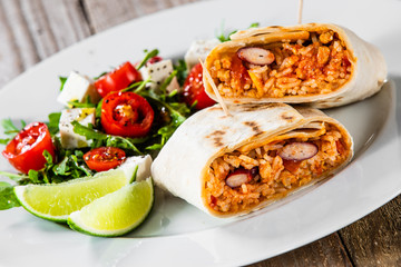 Burrito with vegetable salad on white plate