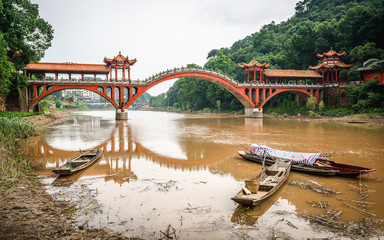 Haoshang arch bridge in oriental Buddha park and small fishing boats on the river in Leshan China