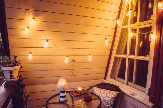 Cute retro wooden nautical style balcony view with small garden table and chair and decorative string party bulbs lights on in the evening.