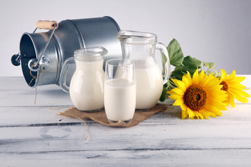 A jug of milk and glass of milk on a wooden table and flower