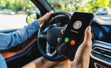 Unknown number calling while car driving. Phone call from stranger. Person holding mobile and...