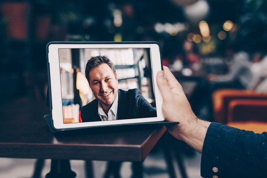 Young man having business meeting via video call in a cafe. Concept of online long distance communication.