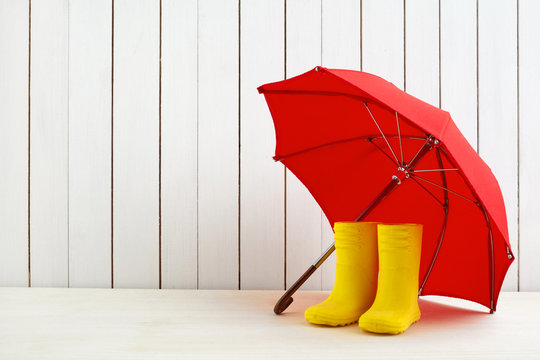 A pair of yellow rain boots and a umbrella on white wooden background