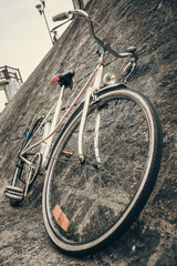 Old bike lying on stone wall