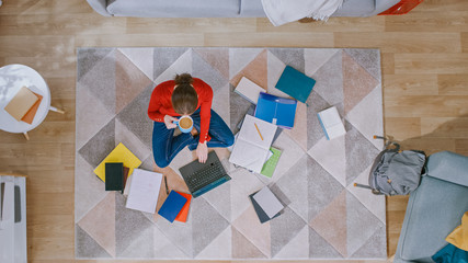 Young Girl in Red Blouse and Blue Jeans is Sitting on a Floor, Working or Studying on a Laptop. Drinks Coffee. Cozy Living Room with Modern Interior with Carpet, Workbooks and Backpack. Top Down.