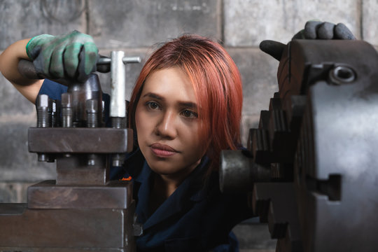 Diverse woman engineer working with heavy industrial machinery - Female factory worker operating production lathe machine - Millennial repair girl inspecting workshop tool - women in workplace concept