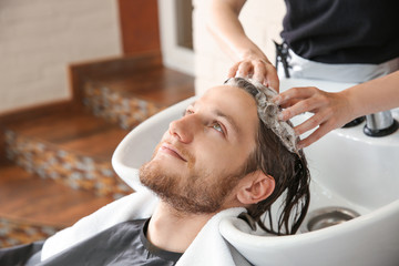 Female hairdresser washing hair of young man in salon