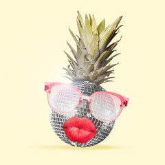 Al alternative view of usual fruits. Pineapple as a disco ball in eyeglasses sending kisses on yellow background. Negative space. Modern design. Contemporary art collage. Concept of music.