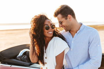 Photo of beautiful multiethnic couple hugging and smiling together while standing by car outdoors