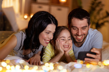 people and family concept - happy mother, father and little daughter with smartphone in bed at night at home