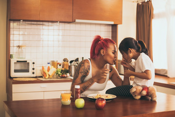 Young mother and kid daughter having breakfast in kitchen.