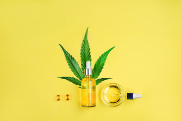 Bottle with CBD oil, pipette, capsules and cannabis leaf on a yellow background. Minimalism, flat lay. Wall mural