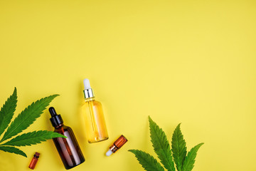 Bottles with CBD oil, a dropper, and leaf marijuana on yellow background. Concept beauty care with hemp oil