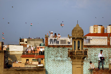 Children fly kites from rooftops as they celebrate Independence Day in the old quarters of Delhi