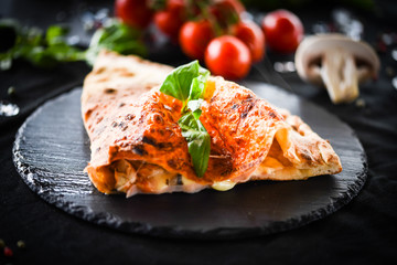 Aluminium Prints Pizzeria tasty italian calzone pizza with fresh ingredients and vegetables