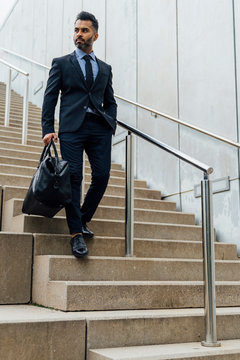 Young Elegant Businessman Walking Down from a Staircase