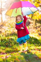 Kid with umbrella playing in autumn rain.