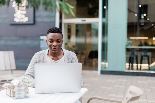 African man working with computer at coffee