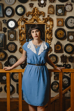 Portrait Of Stylish Woman Wearing Vintage Dress In Front Of The Wall With Clocks