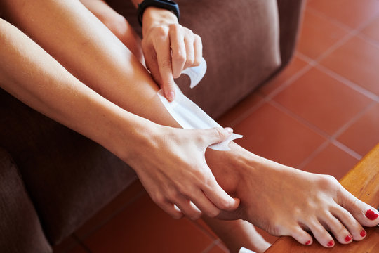 Woman depilating legs with wax strips