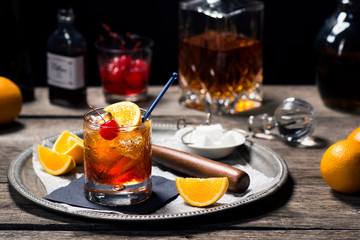 Old Fashioned Cocktail On Ice with Cherry and Orange Garnish and Ingredients on Bar in Dark Background Wall mural