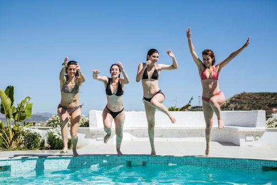 Young women enjoying the summer time at pool, jumping into the water