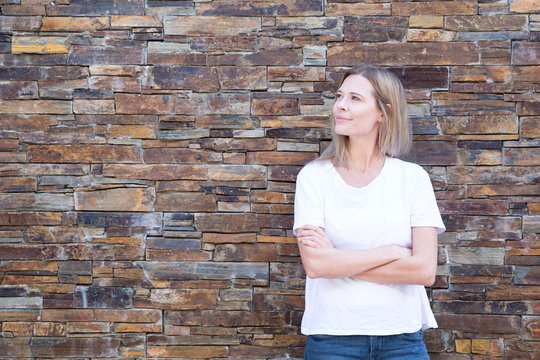 Woman in front of a wall looking sideways, arms crossed