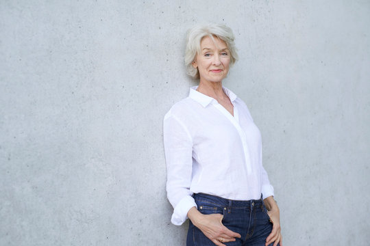 Portrait of relaxed mature woman wearing white shirt leaning against concrete wall