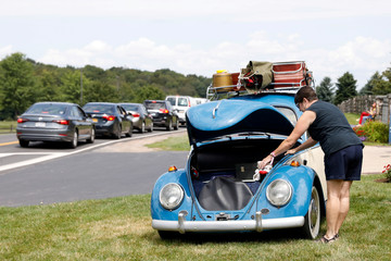 Mary Zavilla checks her and her husband's 1964 Volkswagen Beetle as attendees arrive at the Bethel Woods Center for the Arts, the original site of the Woodstock Festival, on its 50th anniversary in Bethel, New York