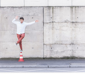 Young man balancing on traffic cone in front of concrete wall