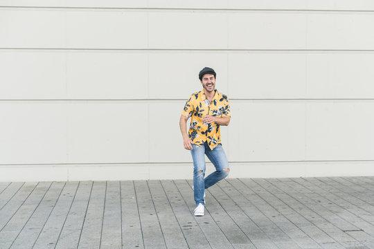 Young man wearing flat hat and aloha shirt, having fun
