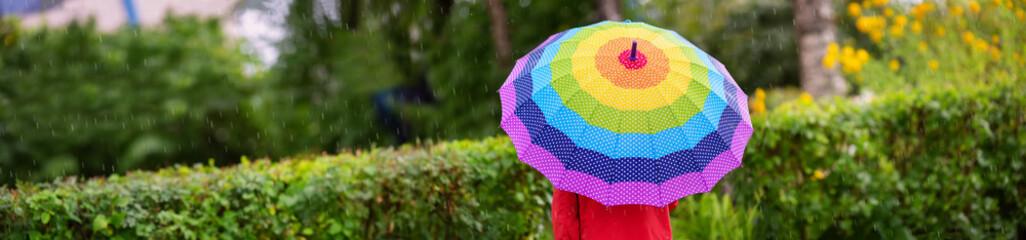 Obraz Boy holding colourful umbrella under rain in summer - fototapety do salonu