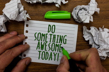 Word writing text Do Something Awesome Today. Business concept for Make an incredible action motivate yourself Hand hold green pen and words on white page paper lobs around on wooden desk